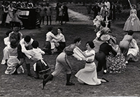 Sixteen young women dance as couples in folk costumes.